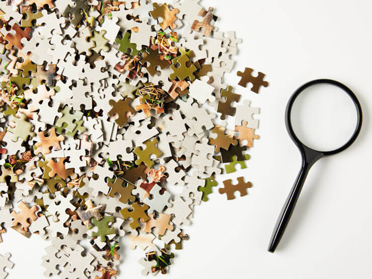 Jigsaw puzzle pieces and a magnifier