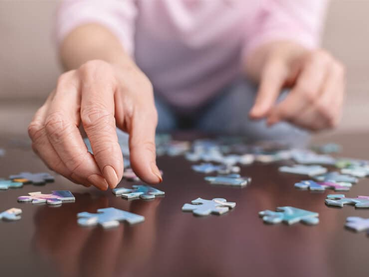Hands of an elderly lady solving a jigsaw puzzle