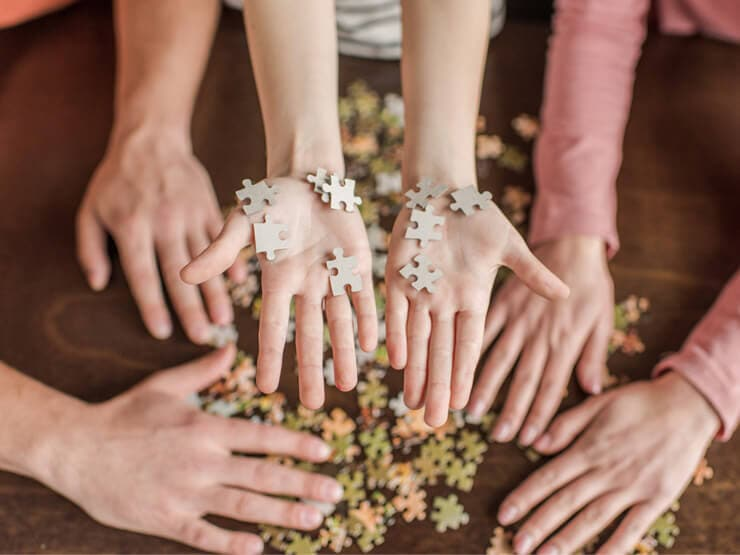 Doing jigsaw puzzles together - view of hands solving a puzzle