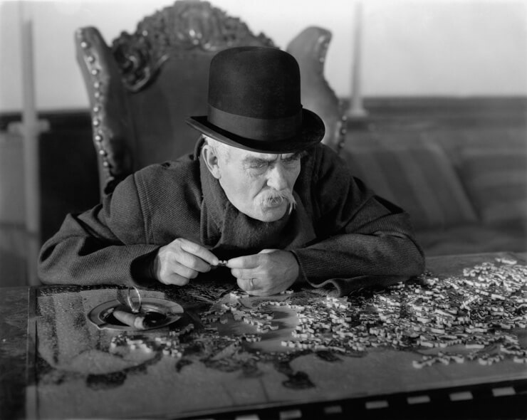 A historical photo of an elderly man solving a jigsaw puzzle
