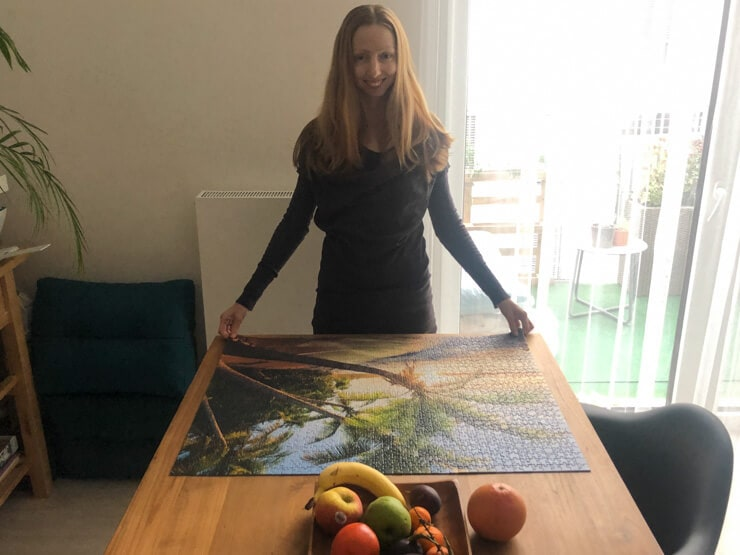 Veronika of Jigsaw Puzzle Queen posing with a finished beach puzzle